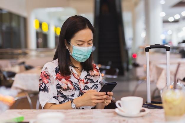 Женщина пассажир в аэропорту носить защитную маску и с помощью мобильного телефона.