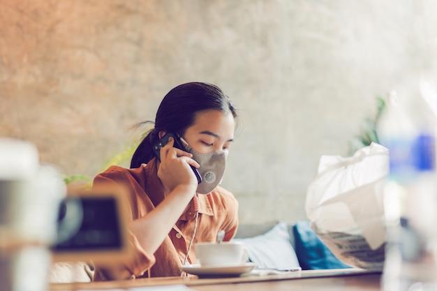 Молодая женщина нося защитную маску говоря на сотовом телефоне, концепцию работы.