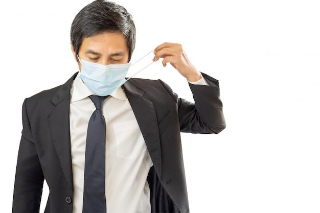 Бизнесмен кладя защитную маску на его сторону на белую стену.