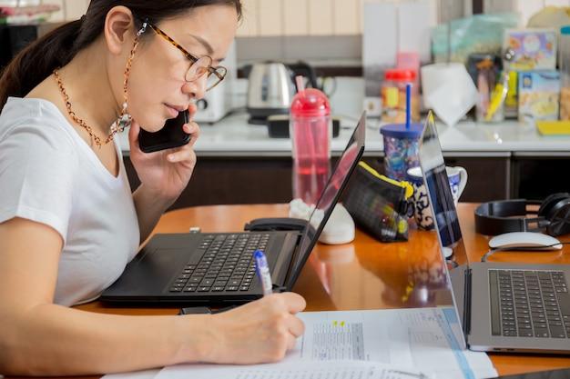 自宅のラップトップで携帯電話で話している眼鏡の美しい女性。