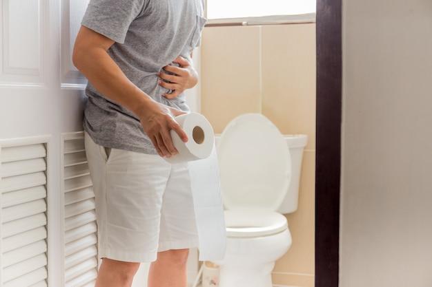 トイレットペーパーを保持している男性には、腹痛コロナウイルスの症状の概念があります。