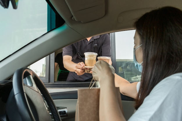 コロナウイルスの発生中にドライブスルーでコーヒーを飲んでいる防護マスクの女性