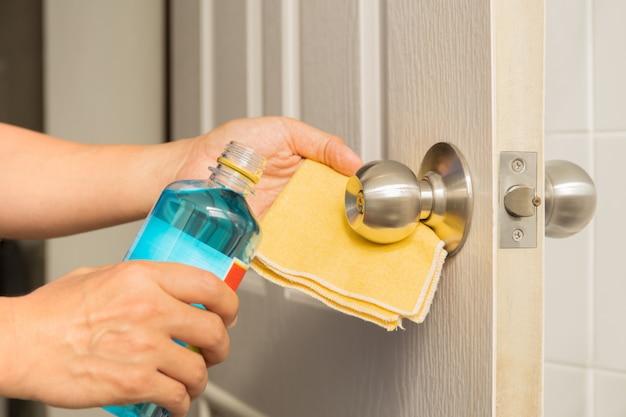 Ручная чистка дверной ручки со спиртовой и желтой салфеткой из микрофибры.