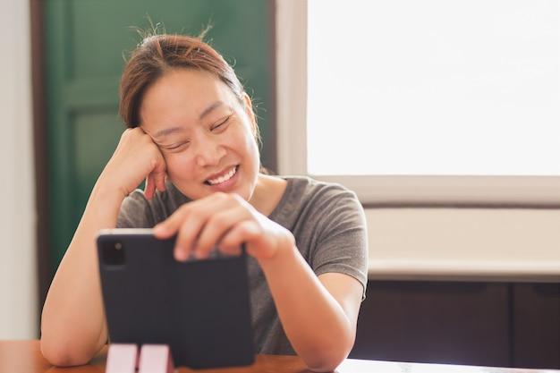 Социальные дистанцирующие счастливые улыбающиеся женщины, используя сотовый телефон видео звонок семьи.
