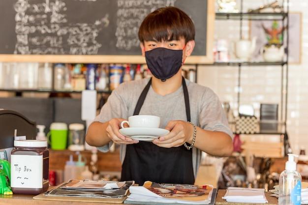 Официант социального бизнеса концептуальной малого бизнеса, где подают кофе для клиентов в кафе.