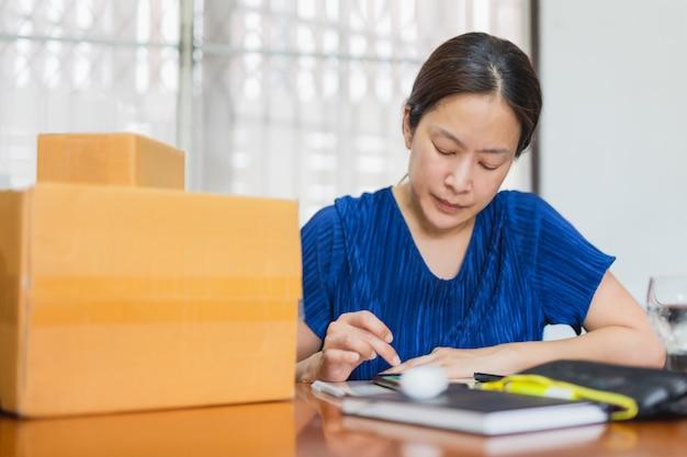 ホームオフィスから顧客への配達パッケージの携帯電話で注文を確認する女性。