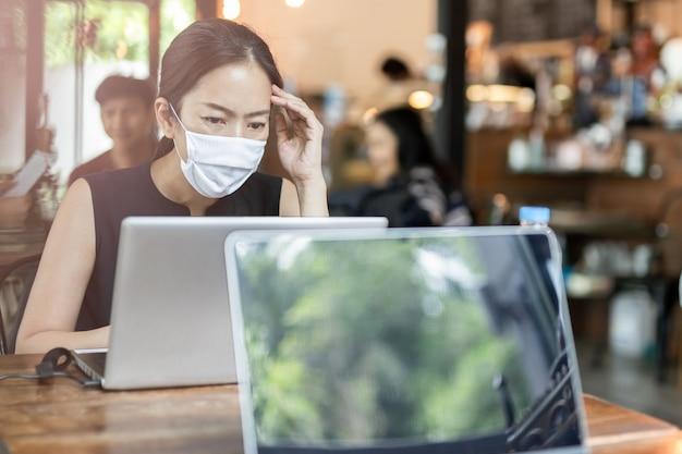 Лицо женщины носить маска для профилактики во время работы на ноутбуке.