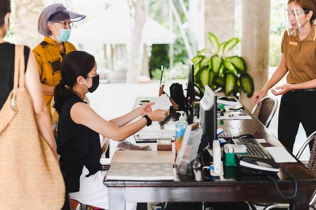 ホテルのゲストに封筒を与えるフェイスシールド付きの選択されたフォーカス受付係。