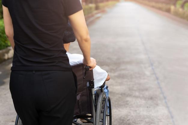 Смотритель проводит время на открытом воздухе с пациентом в инвалидной коляске