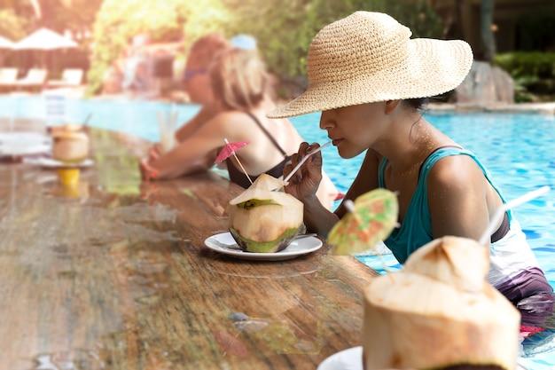 スイミングプールでココナッツドリンクを持つ帽子を持つアジアの女性