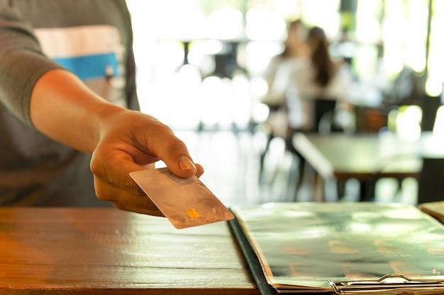 コーヒーショップでクレジットカードで支払っている男性顧客。