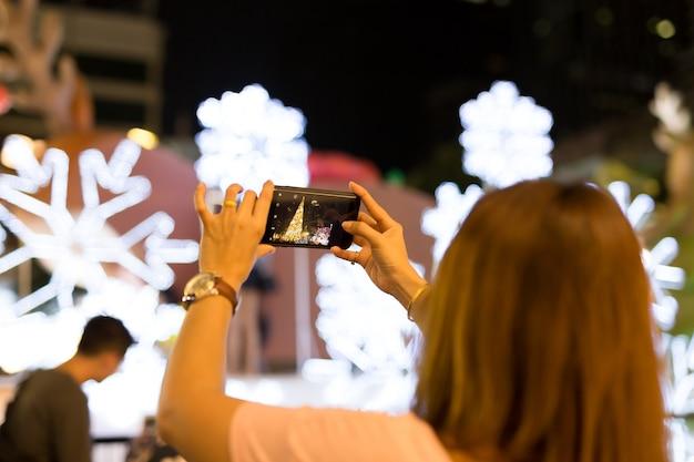 女性の手は携帯電話を持って、クリスマスツリーと光の写真を取る。