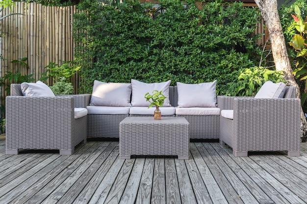 Большой террасный патио с садовой мебелью из ротанга в саду на деревянном полу.