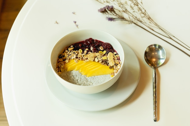 テーブル上の甘いプディングとフルーツのスムージーボウルのヘルシーな朝食。