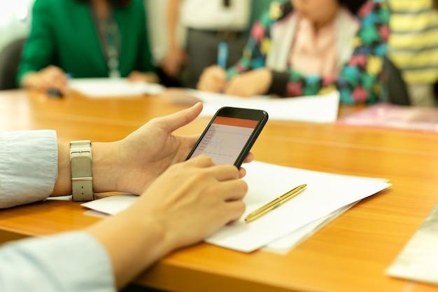 ビジネスの人々のグループと株価グラフと携帯電話を使用して手。