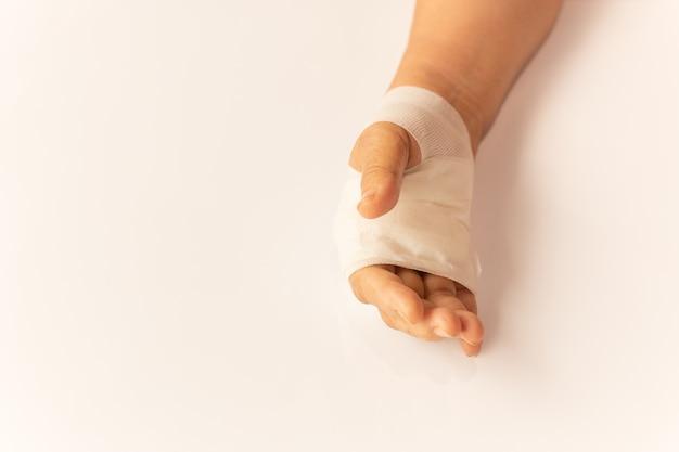高齢女性の手が病院の白いテーブルの上に包帯で怪我をしています。