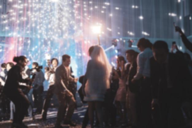 ぼやけてコンセプト幸せな新郎と新婦のゲストとのウェディングパーティーで踊る