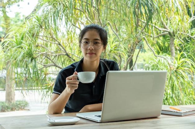 カフェでテーブルの上のノートパソコンとコーヒーを保持している美しい若いアジアの女の子。