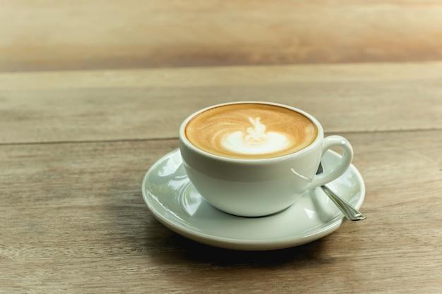 Чашка кофе с пеной на деревянном столе.