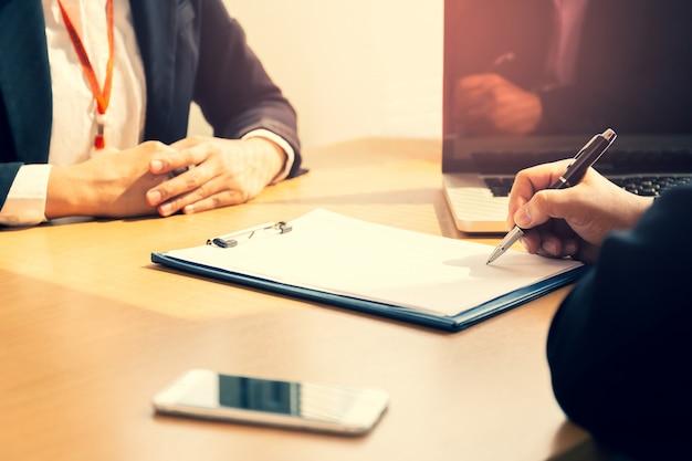 木製の机の上のクロスプロセスでビジネス成功した署名契約。