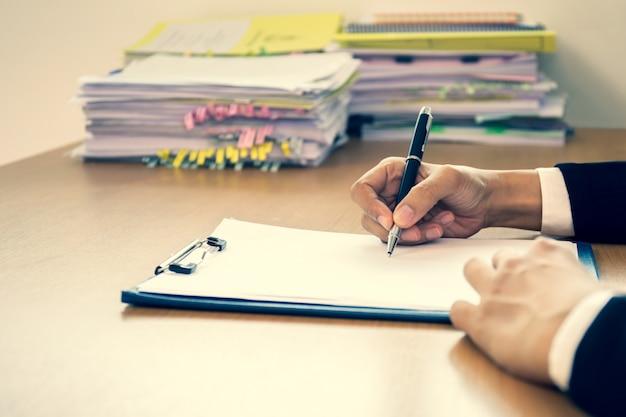 ビジネス成功した手のオフィスの木製の机の上の契約書に署名します。