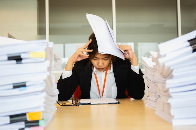 Коммерсантка отдыхая рука на головных глазах близко с кучей обработки документов.