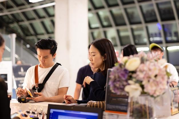 アジアカップルがフロントでホテルの部屋のための法案に署名します。