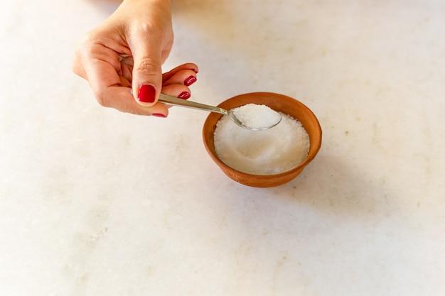 Рука женщины держа ложку полный концепции здравоохранения сахара.