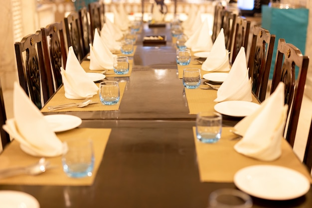 ナプキンとディナーテーブルの上の水の空のグラスの選択されたフォーカス。