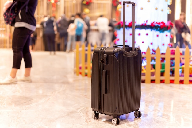 ぼかしの背景でホテルのロビーでチェックインする人々のグループの荷物袋。