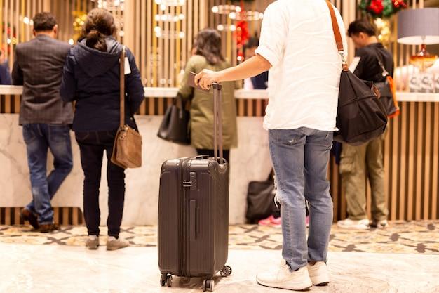 ホテルのフロントでチェックインを待っているスーツケースとパスポートを保持している選択フォーカス男。