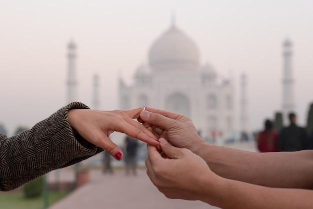 バックグラウンドでタージ・マハルと彼の妻の指に婚約指輪をかぶる人。