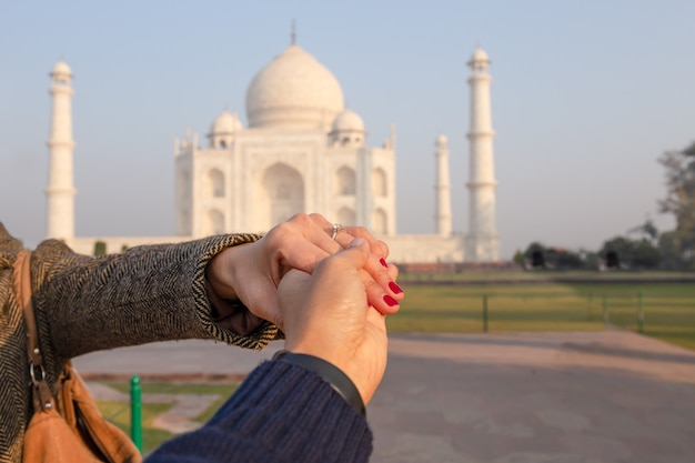 バックグラウンドでタージ・マハルと結婚指輪を示す彼の妻の手を握って男。