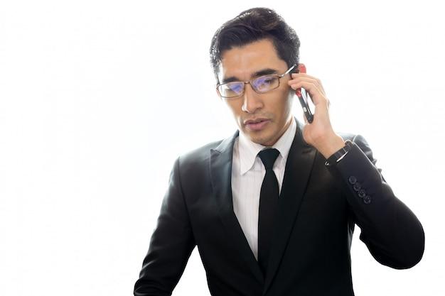 アジア系のビジネスマンが白い背景で隔離の携帯電話で話しています。
