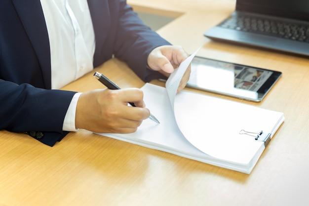 実業家のオフィスの机の上にペンで契約書に署名します。