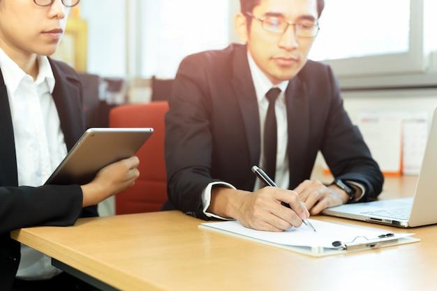 ビジネスエグゼクティブは、オフィスの机で秘書と契約を締結します。