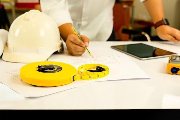 テーブルの上のタブレットコンピューターと青写真に取り組んでいる建築家の手。
