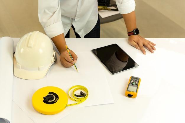 テーブルの上のタブレットコンピューターと青写真に取り組んでいる建築家の上から見る手。
