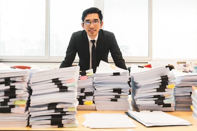 フォアグラウンドで書類の山が付いているオフィスに立っているスーツのビジネスマン。