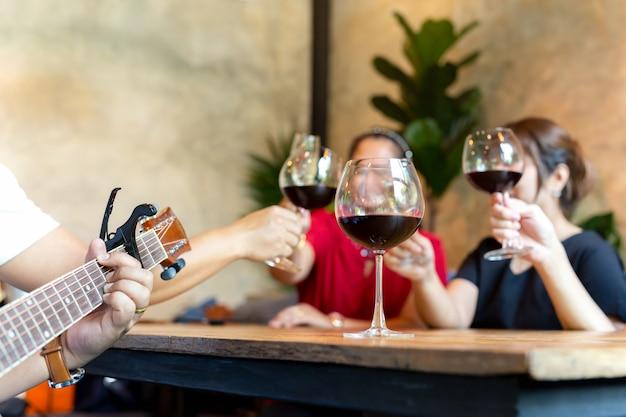 赤ワインを飲みながら祝うとギターを弾く友人のグループ。