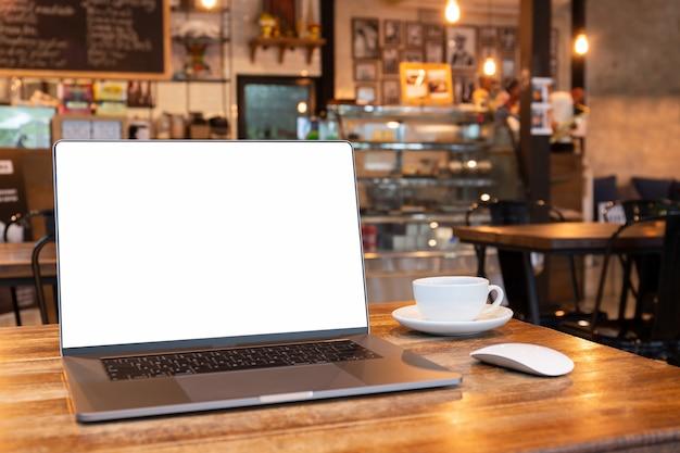 マウスとコーヒーショップの木製テーブルの上のコーヒーカップを持つ空白の画面ノートパソコン。