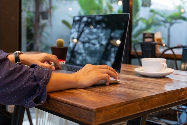 カフェのテーブルでラップトップに取り組んでいるコンピューターのマウスを使用している人。