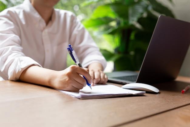 木製のテーブルの上のマウスをノートパソコンと手記入書類フォーム契約。