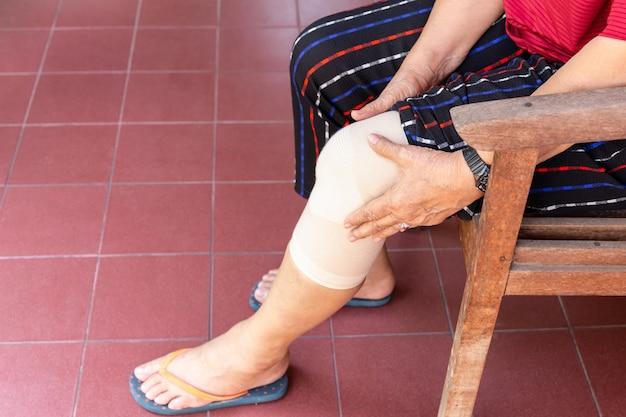 包帯圧縮膝装具を持つアジアの年配の女性は怪我をサポートします。
