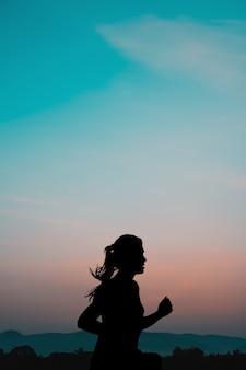 山の自然の背景と日の出を走っている若い女性。
