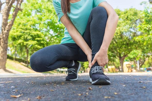 若い女性は公園を走っている間彼の足に痛みがあります。