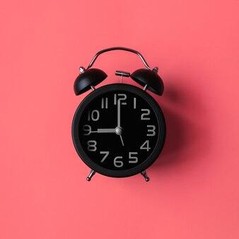 ピンクの背景に黒の目覚まし時計。