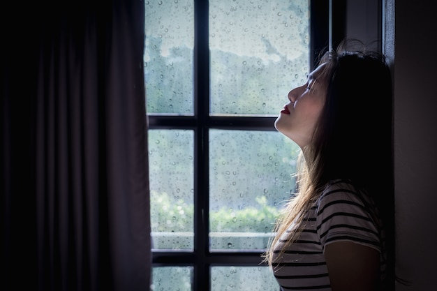 Разбитое сердце молодая женщина плачет в темной комнате с дождливым сезоном.