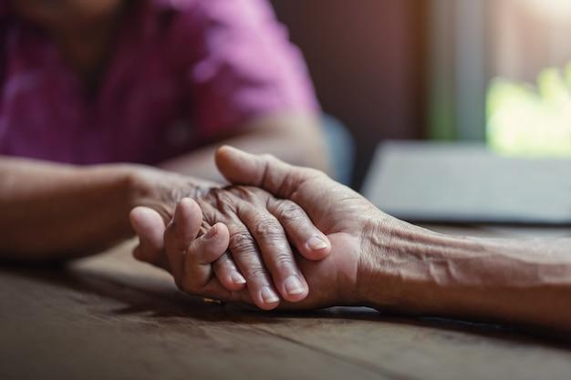 高齢者のカップルは手を持っている、一緒に世話をするの概念。