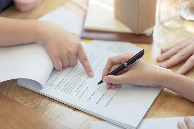 Женщина, ставя подпись договора подписи, договор покупки недвижимости